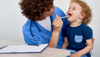 Portrait of cute little boy opening mouth for checkup sitting in doctors lap against white background