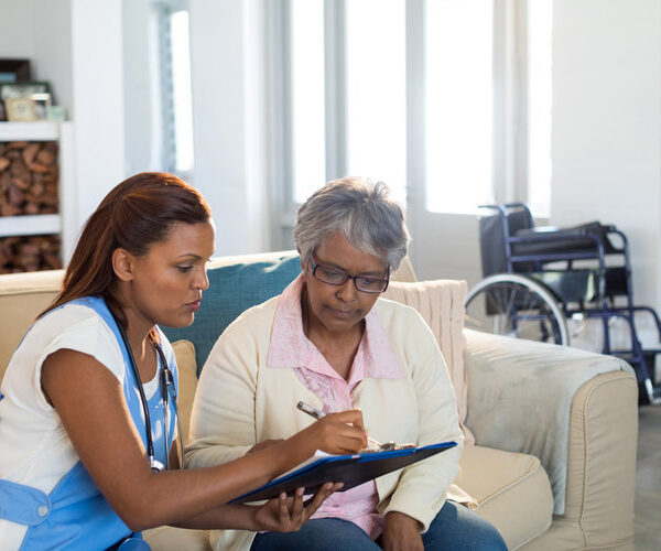 Doctor explaining medication on clipboard to senior woman in living room at home