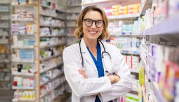 Portrait of mature woman pharmacist at pharmacy wearing labcoat with stethoscope. Happy smiling doctor standing in modern pharmacy drugstore. Friendly young pharmacist owner standing in shop and looking at camera.