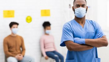 Portrait Of Confident African American Doctor In Medical Mask Standing In Hospital Room, Posing Looking At Camera. Physician Medic And Nurse Profession, Clinic Staff Concept. Empty Space For Text